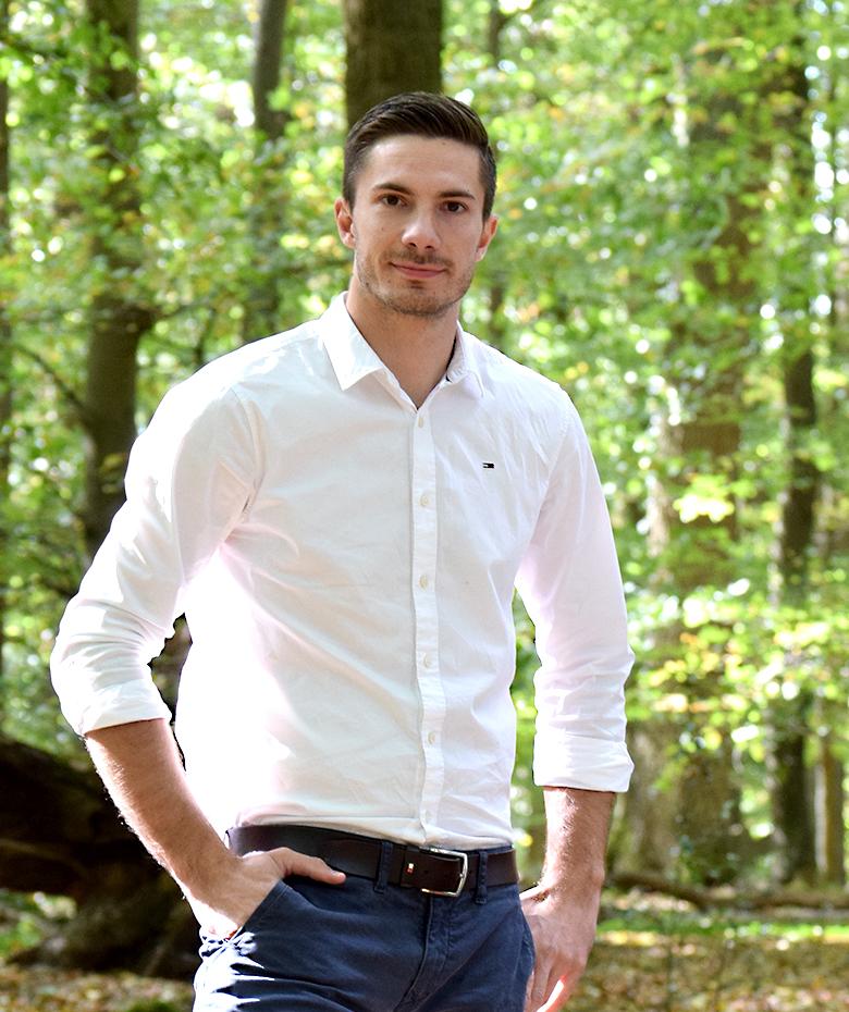 junger Mann mit weißem Hemd steht im Wald