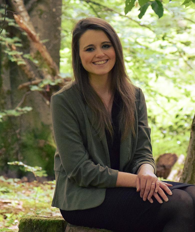 junge Frau mit Blazer sitzt auf Baumstumpf im Wald