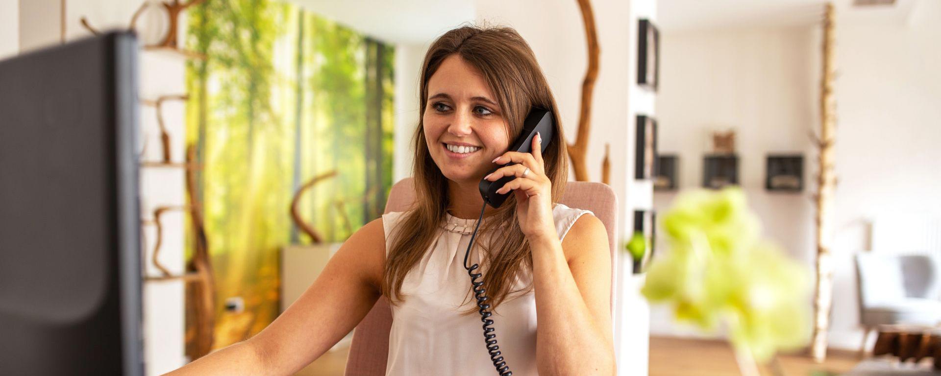 junge Frau telefoniert am Schreibtisch