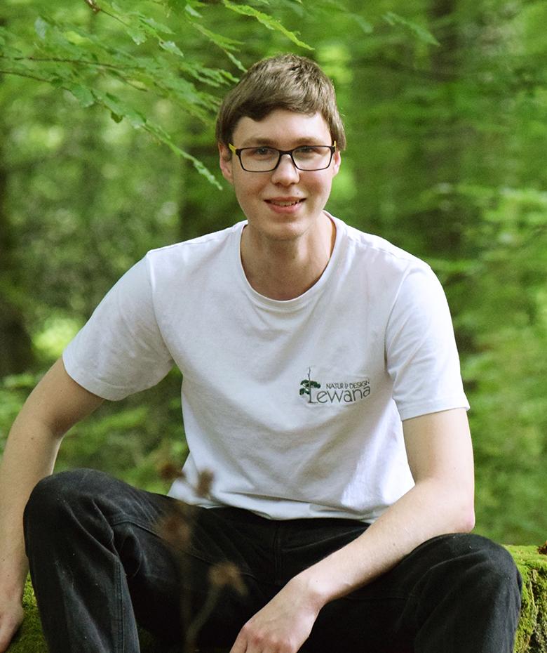 Junge mit Brille und weißem Shirt sitzt auf Baumstumpf im grünen Wald